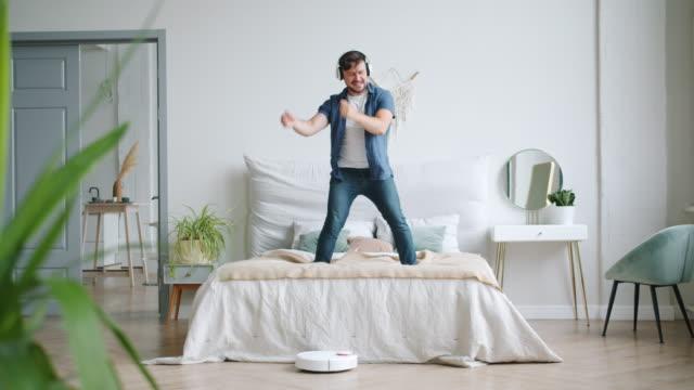 Man in headphones dancing on bed while robotic vacuum cleaner vacuuming floor