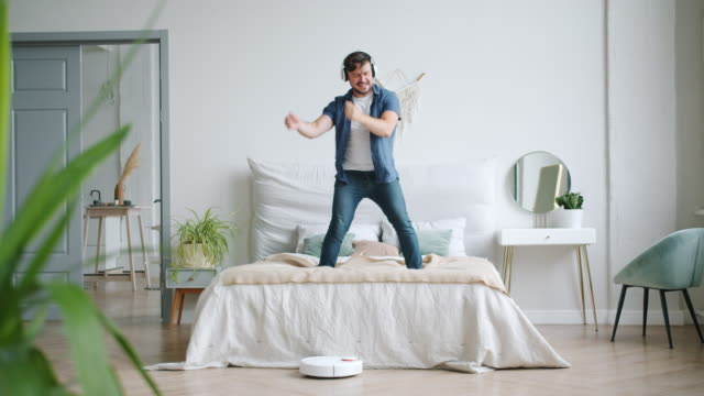 Man in headphones dancing on bed while robotic vacuum cleaner vacuuming floor Man in headphones is dancing on bed having fun while robotic vacuum cleaner is vacuuming floor in apartment. Modern devices, lifestyle and housework concept. headphones stock videos & royalty-free footage