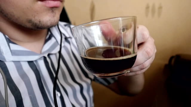 man in headphones listening to music and drinking coffee at the computer. Slowmotion video