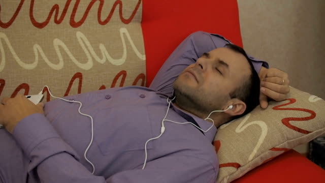 a man in headphones listens to music on a smartphone and falls asleep. dream of relaxation. businessman resting to music lying on the sofa. - sonnecchiare video stock e b–roll