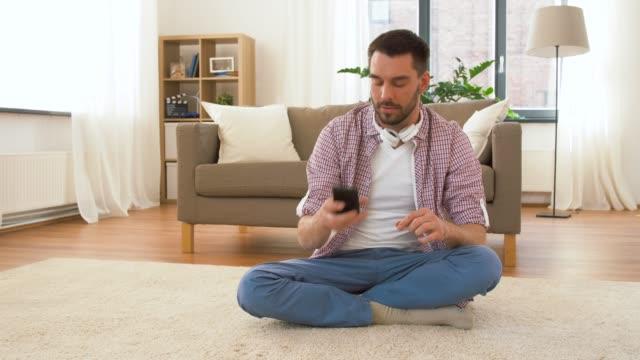 man i hörlurar mediterar i lotus pose hemma - lotusställning bildbanksvideor och videomaterial från bakom kulisserna