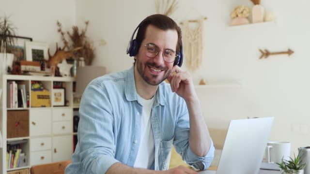 man in headphones sitting near laptop smiling looking at camera - didattica a distanza video stock e b–roll