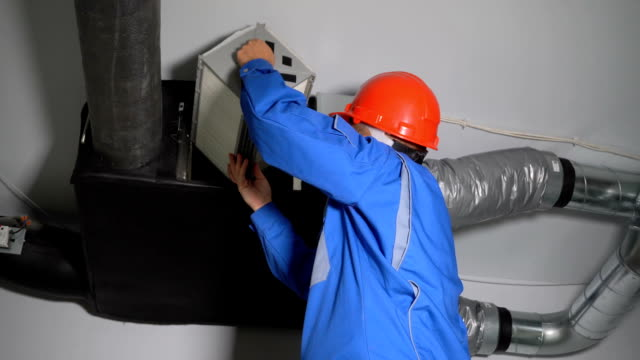 Man in helmet changing air quality control device. Worker change filter