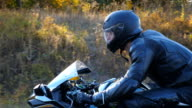 istock Man in helmet riding on a motorbike at highway with sun flares at background. Motorcyclist driving his motorcycle on autumn country road. Slow motion Side view Close up 1223155355