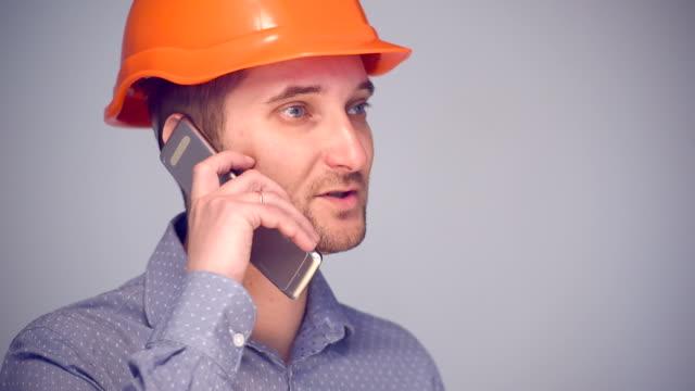 Man in helmet talks on mobile phone video