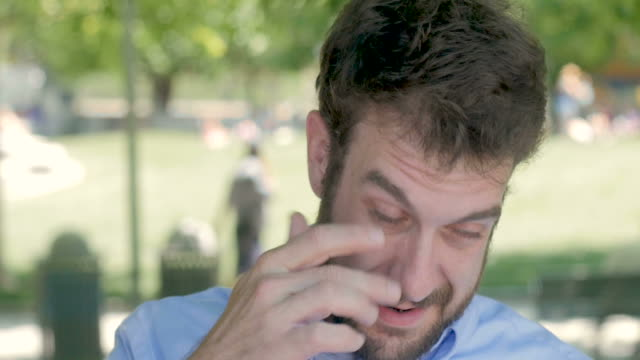 A man in his early 30s rubbing his eye outside video
