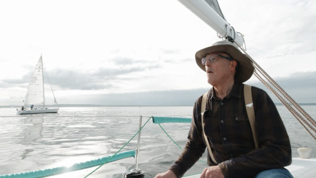 A Man in His Sixties Pulls a Rope Tight in a Winch on His Sailboat on the Puget Sound in Washington while His Crew Sits on the Deck Looking at the View