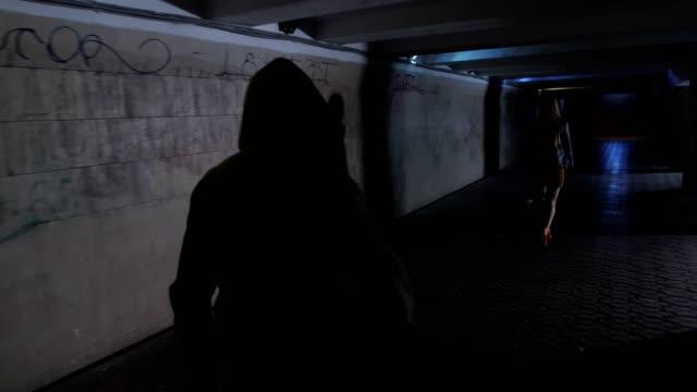 mannen i hoodie jagar kvinna i mörk tunnel - kriminell bildbanksvideor och videomaterial från bakom kulisserna