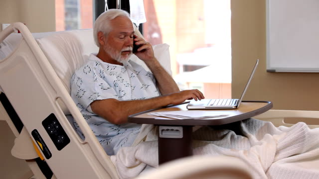 Man in hospital bed uses phone and laptop comput video