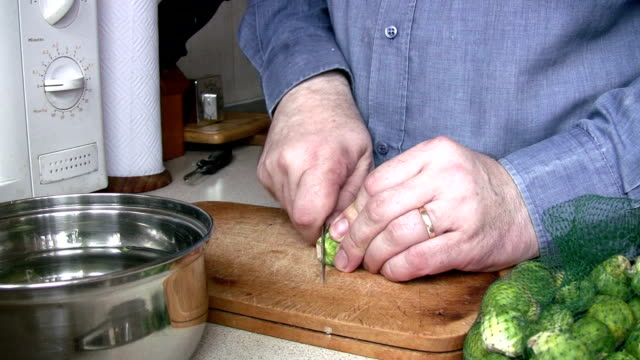 stockvideo's en b-roll-footage met man in kitchen preparing brussels sprouts for cooking - spruitjes