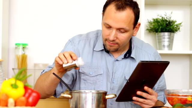 vidéos et rushes de homme dans la cuisine à l'aide d'une tablette ordinateur - recette