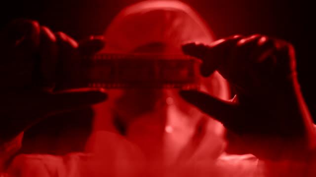 Mann im Labor Kostüm beobachten Kamerarolle, Foto in rotes Licht zu entwickeln – Video