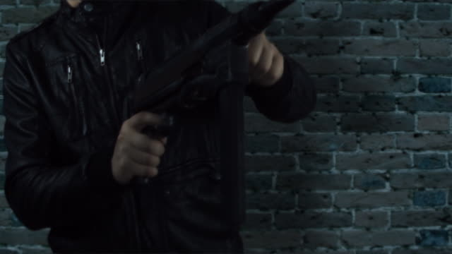 man in leather jacket with machine gun HD video