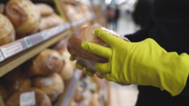 man in mask and rubber gloves choosing bread in a supermarket - rękawiczka filmów i materiałów b-roll
