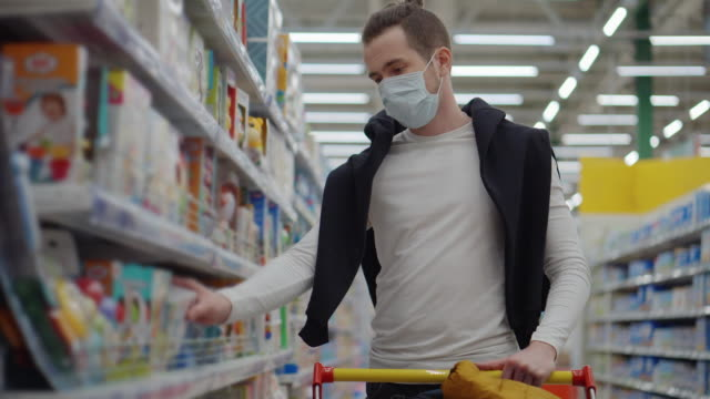 Man in mask shopping for baby care products in the supermarket - vídeo