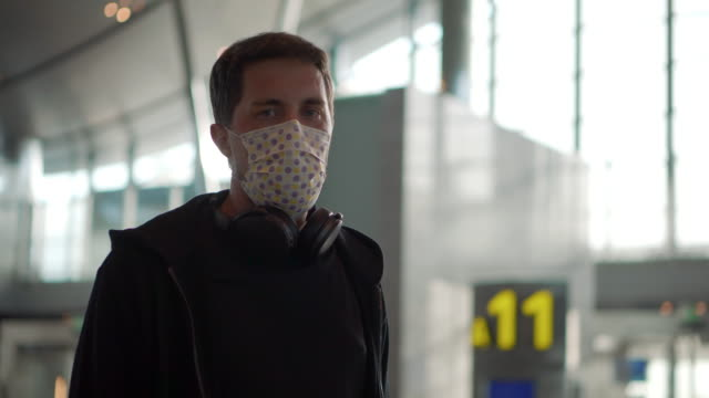 Man in medical mask at the airport - vídeo