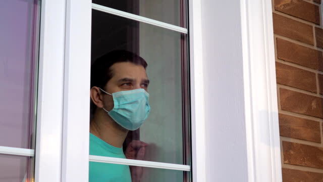 Man in medical mask stay at home. Self isolation video