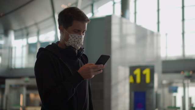 Man in medical mask using cellphone. Precaution during epidemic - vídeo