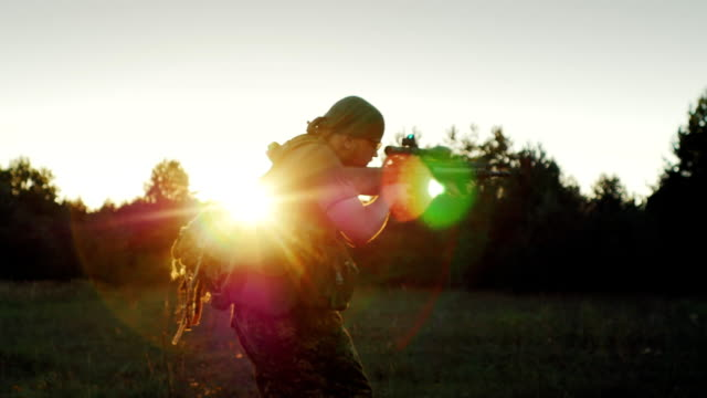 A man in military uniform attacked, running with a gun in the sunset. Back view video