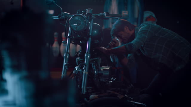 Hombre en motocicleta taller edificio una bicicleta. - vídeo
