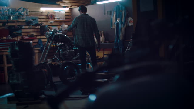 mann auf motorrad-workshop gebäude ein fahrrad - garage stock-videos und b-roll-filmmaterial