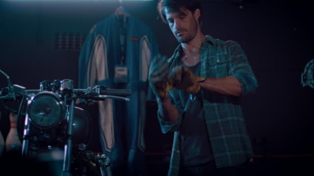 Man in motorcycle workshop grinding a piece of metal video