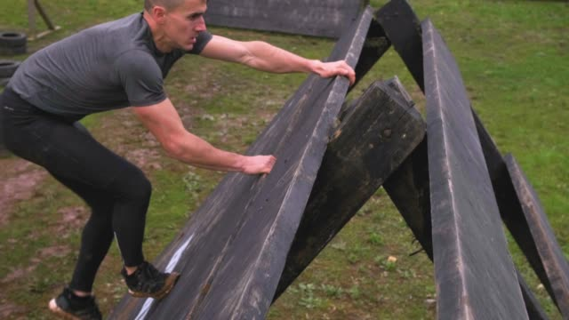 Man in obstacle course climbing pyramid obstacle Male participant in an obstacle course climbing a pyramid obstacle conquering adversity stock videos & royalty-free footage