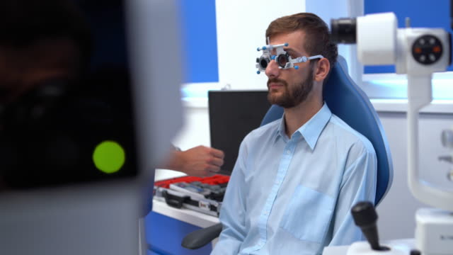 vidéos et rushes de l'homme dans le magasin d'oculistes vérifie sa vue - réfracteur
