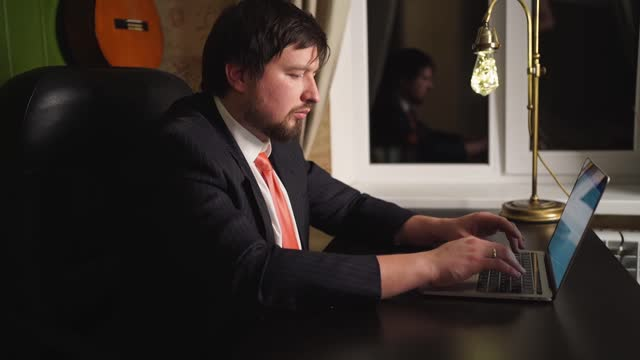 A man in pants, a jacket and a tie works at the computer at night in home office