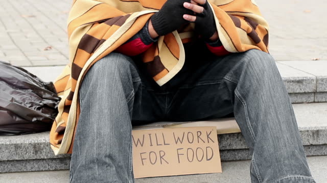 Man in park with ready to work for food sign, homeless begging, poverty, sadness video