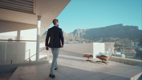 Man in penthouse looking over the city A man walking on the rooftop of his penthouse. He looks over the city. Its a beautiful summerday and in the background a table mountain can be seen. apartment stock videos & royalty-free footage