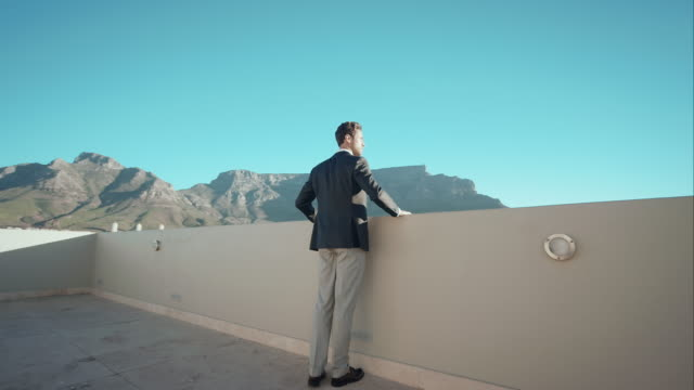 Man in penthouse looking over the city video