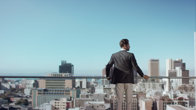 Man in penthouse looking over the city