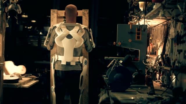 man in powered exoskeleton in workshop - манипулятор робота производственное оборудование стоковые видео и кадры b-roll