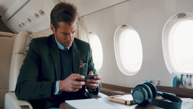 Man in private jet airplane Elegant man sitting inside private jet airplane and using mobile phone. Headphones are on the table. private airplane stock videos & royalty-free footage