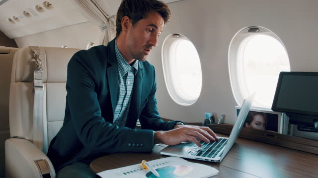 Man in private jet airplane Young businessman sitting inside private jet airplane and using laptop during the flight. financial occupation stock videos & royalty-free footage