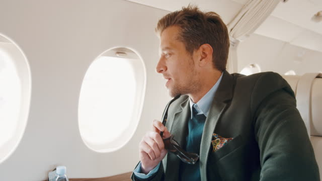 Man in private jet airplane Elegant man sitting inside private jet airplane, holding sunglasses and looking outside the window. private airplane stock videos & royalty-free footage