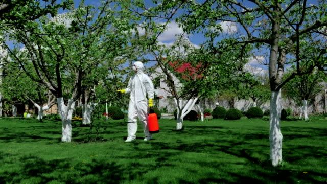 uomo in abbigliamento protettivo lavorare in giardino - insetticida video stock e b–roll
