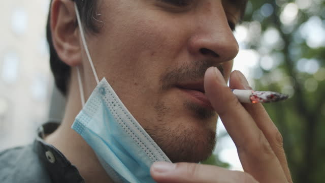 Man in protective face mask smoking a cigarette