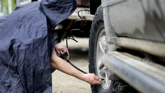 mannen i regnrock pumpa hjulen på suv på vägarna - barometer bildbanksvideor och videomaterial från bakom kulisserna