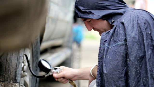 mann im regenmantel pumpen räder suv am straßenrand - inflation stock-videos und b-roll-filmmaterial