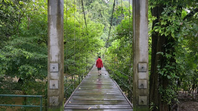 Man in red coat walking cross wooden suspension bridge on river in national park