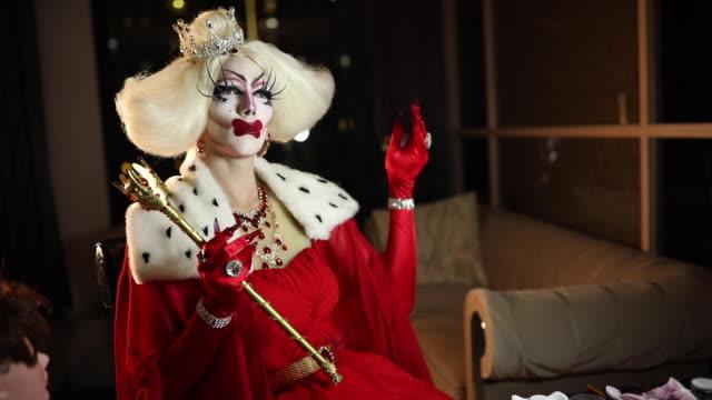 stockvideo's en b-roll-footage met man in rode jurk met lange nagels zittend in donkere kamer - drag queen
