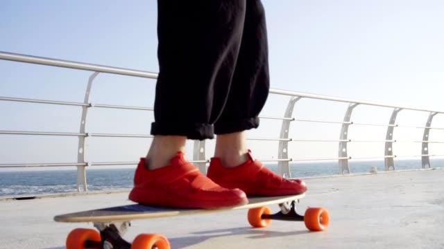stockvideo's en b-roll-footage met man in rode sneakers schaatsen op longboard aan zee - running shoes
