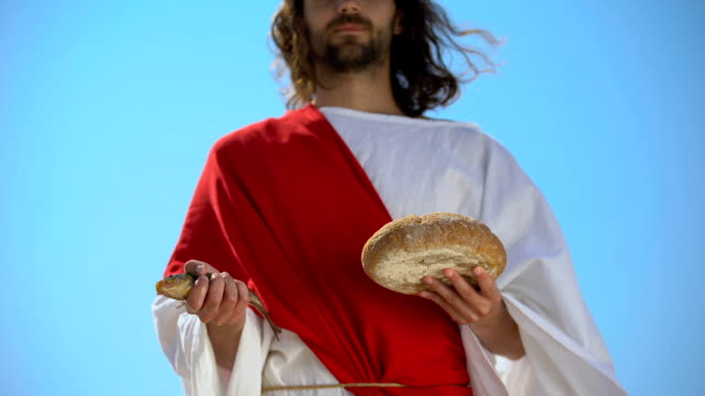 Man in robe holding fish and bread, charity concept to feed hungry, generosity Man in robe holding fish and bread, charity concept to feed hungry, generosity feeding stock videos & royalty-free footage