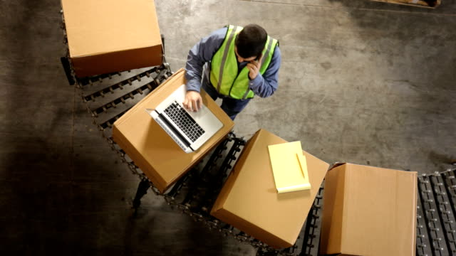 Man in shipping warehouse uses laptop, overhead view video