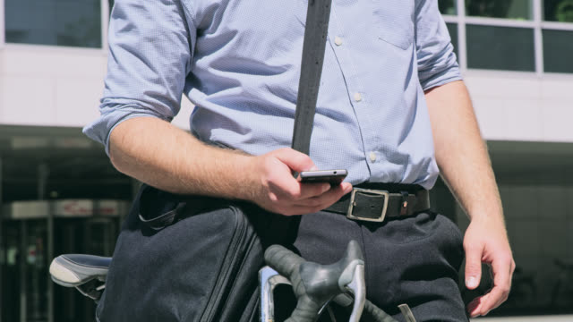 DS Man in shirt using a smart phone in front of the office building video