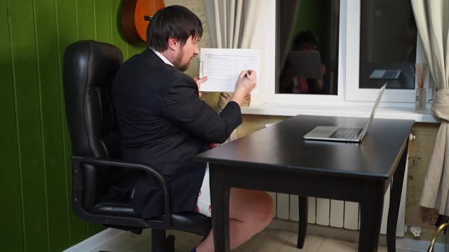 A man in shorts, a jacket and a tie draws a graph and leads a conference online