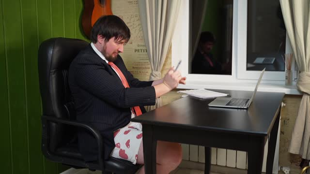 man in shorts, a jacket and a tie rips paper with graphs on a conference online