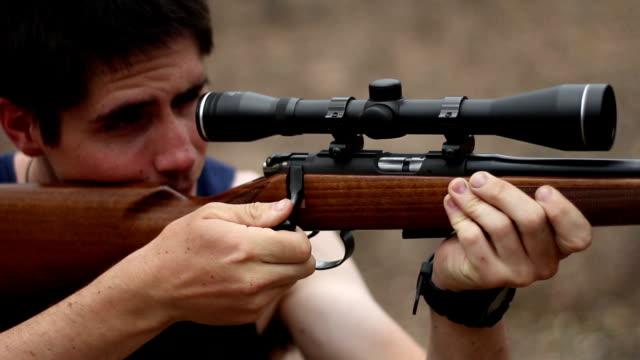 man in singlet shooting rifle video